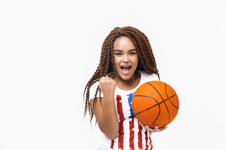 Portrait of beautiful african american woman rejoicing and holding basketball during game while standing isolated against white wall
