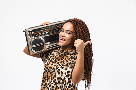 Image of stylish african american woman smiling and holding vintage boombox with cassette tape on her shoulder isolated against white background