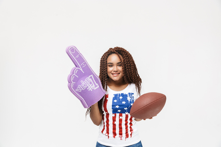 Portrait of funny african american woman holding number one fan glove and rugby ball while standing isolated against white wall Imagens