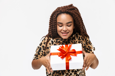Image of glamorous african american woman smiling and holding present box with bow while standing isolated against white background