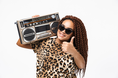 Image of glamorous african american woman smiling and holding vintage boombox with cassette tape on her shoulder isolated against white background