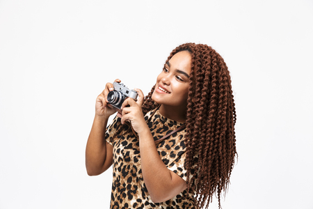 Image of beautiful african american woman smiling and photographing on retro camera while standing isolated against white background