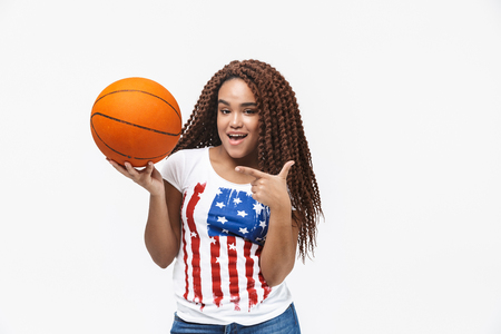 Portrait of pretty african american woman rejoicing and holding basketball during game while standing isolated against white wall