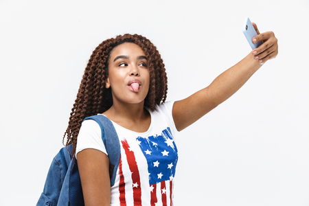 Portrait of playful african american woman wearing backpack smiling and taking selfie photo on cellphone while standing isolated against white wall