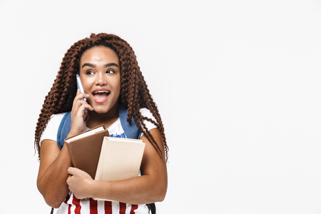 Portrait of brunette african american woman wearing backpack talking on cellphone while holding studying books isolated against white wall Imagens