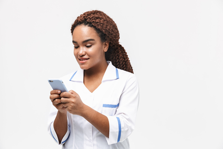 Image of smiling african american nurse or doctor woman wearing medical coat holding and using cellphone isolated against white background