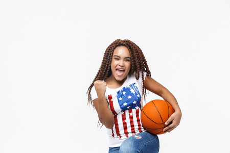 Portrait of delighted african american woman rejoicing and holding basketball during game while standing isolated against white wall
