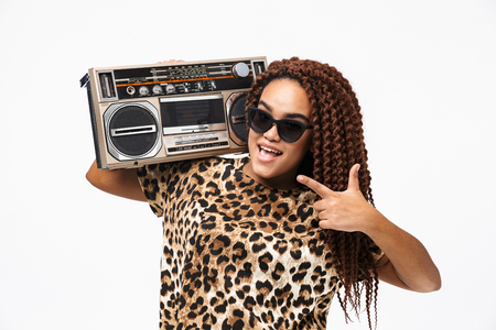 Image of african american hipster woman smiling and holding vintage boombox with cassette tape on her shoulder isolated against white background Imagens