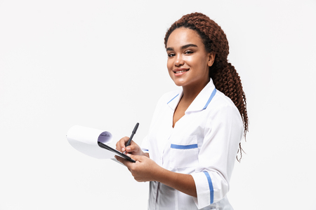 Image of smiling african american nurse or doctor woman writing medical case report isolated against white background Imagens