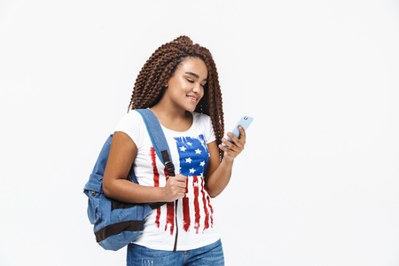 Portrait of attractive african american woman wearing backpack smiling and holding cellphone while standing isolated against white wall