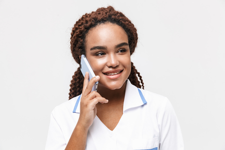 Image of happy african american nurse or doctor woman wearing medical coat holding and talking on cellphone isolated against white background