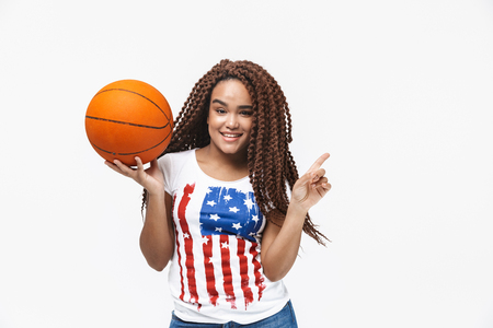 Portrait of energetic african american woman rejoicing and holding basketball during game while standing isolated against white wall