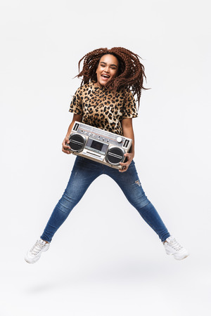 Image of happy african american woman smiling and holding vintage boombox with cassette tape isolated against white background