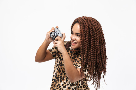 Image of happy african american woman smiling and photographing on retro camera while standing isolated against white background