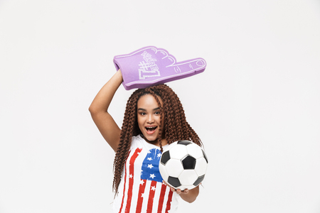 Portrait of beautiful african american woman holding number one fan glove and soccer ball while standing isolated against white wall