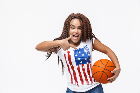 Portrait of attractive african american woman holding basketball during game while standing isolated against white wall