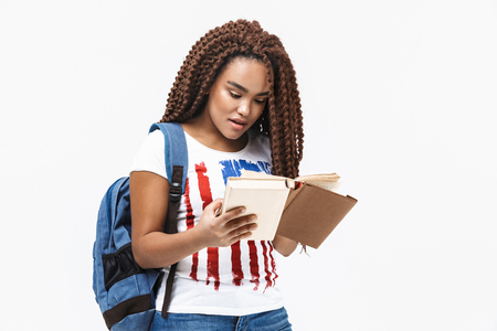 Portrait of young african american woman wearing backpack reading book while studying in college standing isolated against white wall Imagens