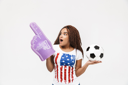 Portrait of energetic african american woman holding number one fan glove and soccer ball while standing isolated against white wall Imagens