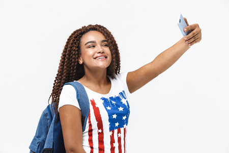 Portrait of cheery african american woman wearing backpack smiling and taking selfie photo on cellphone while standing isolated against white wall