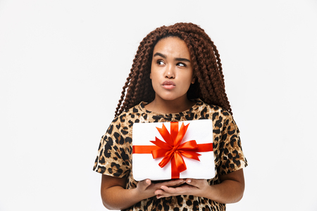 Image of lovely african american woman smiling and holding present box with bow while standing isolated against white background