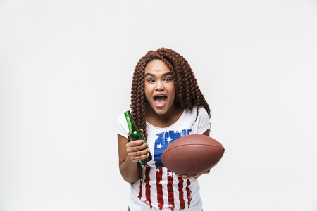 Portrait of joyous african american woman holding rugby ball and beer bottle during game isolated against white wall