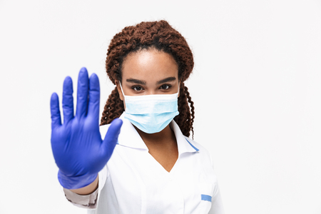 Image of young african american nurse or doctor woman wearing medical face mask and disposable gloves showing stop gesture isolated against white background