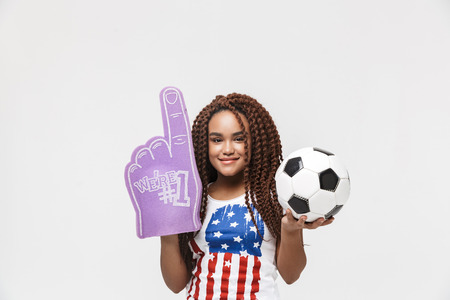 Portrait of active african american woman holding number one fan glove and soccer ball while standing isolated against white wall