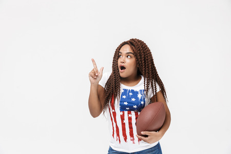 Portrait of excited african american woman holding rugby ball during game while standing isolated against white wall