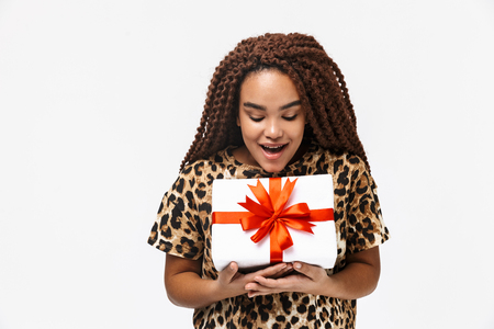 Image of excited african american woman smiling and holding present box with bow while standing isolated against white background Imagens