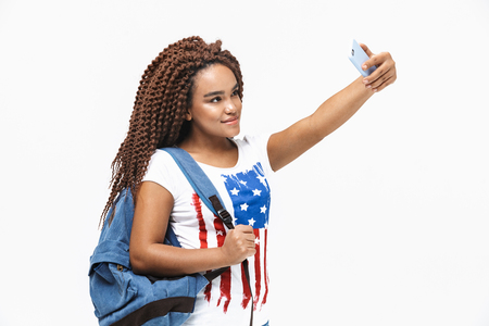Portrait of beautiful african american woman wearing backpack smiling and taking selfie photo on cellphone while standing isolated against white wall