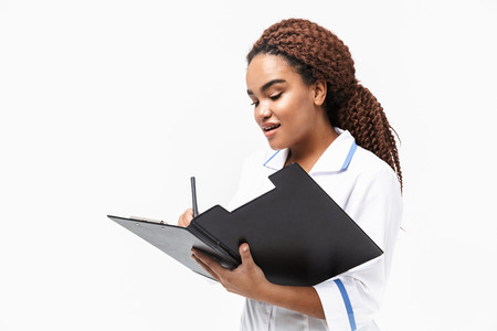 Image of happy african american nurse or doctor woman writing medical case report isolated against white background