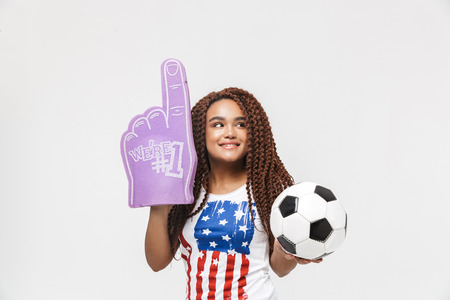Portrait of attractive african american woman holding number one fan glove and soccer ball while standing isolated against white wall Imagens