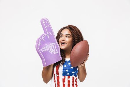 Portrait of delighted african american woman holding number one fan glove and rugby ball while standing isolated against white wall