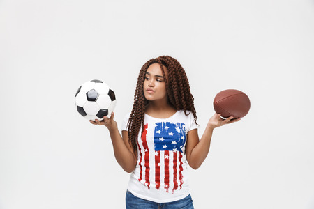 Portrait of cheerful african american woman holding rugby and soccer balls while standing isolated against white wall Imagens