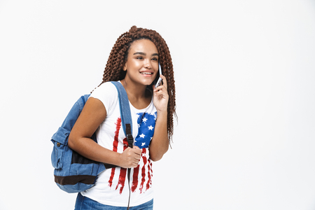 Portrait of cute african american woman wearing backpack smiling and talking on cellphone while standing isolated against white wall
