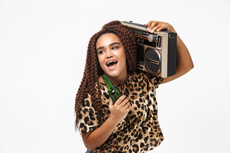 Image of joyous african american woman smiling and holding vintage boombox with cassette tape on her shoulder isolated against white background Imagens