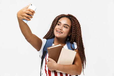 Portrait of joyous african american woman wearing backpack taking selfie photo on cellphone while holding studying books isolated against white wall 免版税图像