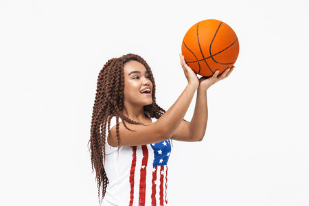 Portrait of young african american woman rejoicing and holding basketball during game while standing isolated against white wall