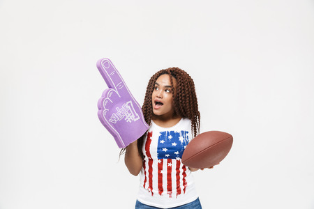 Portrait of brunette african american woman holding number one fan glove and rugby ball while standing isolated against white wall