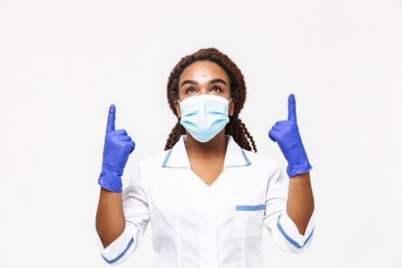 Image of happy african american nurse or doctor woman wearing medical face mask and disposable gloves pointing fingers at copyspace isolated against white background 免版税图像