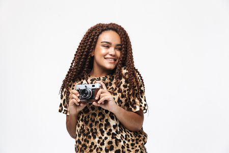 Image of brunette african american woman smiling and photographing on retro camera while standing isolated against white background