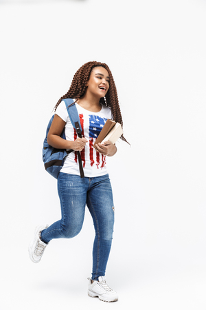 Portrait of brunette african american woman wearing backpack walking while holding studying books isolated against white wall
