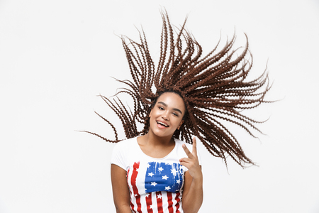 Portrait of ecstatic african american woman having fun and shaking her afro hairstyle while standing isolated against white wall