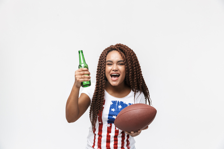 Portrait of delighted african american woman holding rugby ball and beer bottle during game isolated against white wall Imagens