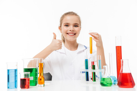 Portrait of joyful little girl in white laboratory coat making chemical experiments with multicolored liquid in test tubes isolated over white background Stockfoto
