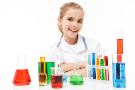 Image of caucasian school girl in white laboratory coat making chemical experiments with multicolored liquid in test tubes isolated over white background