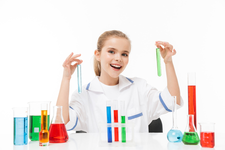 Portrait of smiling little girl in white laboratory coat making chemical experiments with multicolored liquid in test tubes isolated over white background Stockfoto