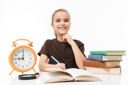 Portrait of cheerful school girl with big alarm clock on desk studying and reading books in class isolated over white background