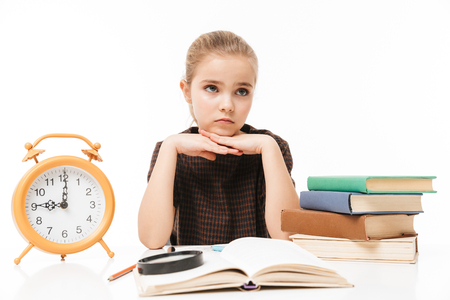 Portrait of pretty school girl with big alarm clock on desk studying and reading books in class isolated over white background Reklamní fotografie