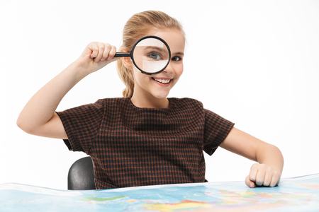 Portrait of european school girl looking at world map through magnifying glass while studying geography in school isolated over white background